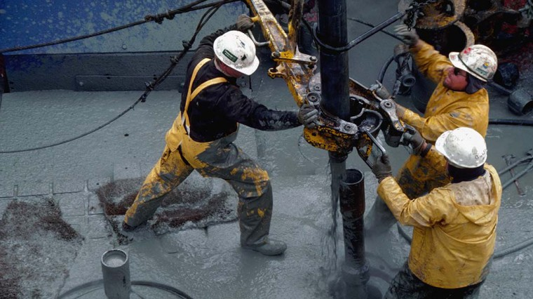 Oil Rig Workers Move Pipe