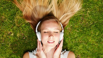 Girl listening to music streaming with headphones in summer on a