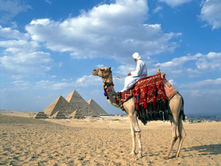 Egypt, Cairo, Man on camel in front of the pyramids of Giza