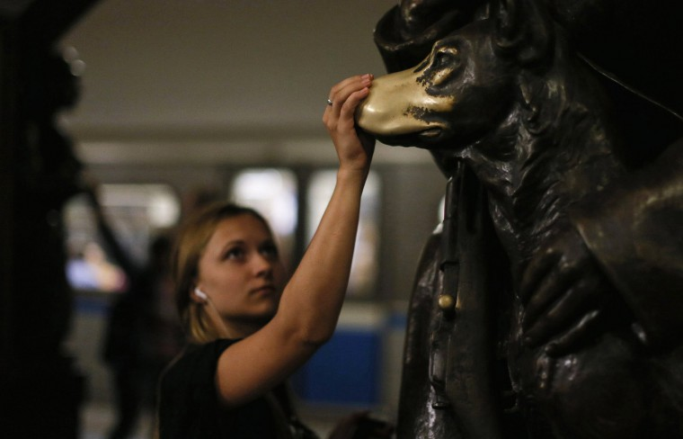 "Woman touches nose of the ""lucky dog"" statue at the Ploshchad Revolyutsii Metro station in Moscow"