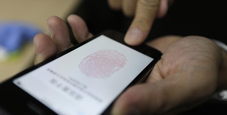 A journalist tests the the new iPhone 5S Touch ID fingerprint recognition feature in Beijing